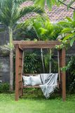 Classic outdoor wooden swing in the green garden with pillows and blanket. Classic outdoor wooden swing in the green garden with pillows and blanket Stock Photos