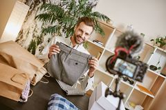 Classic pants. Positive male fashion blogger holding stylish gray trousers while making new content for his fashion blog. Youtube. Instagram. Social media stock photo