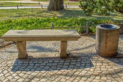 Classic park bench made of stone with trash royalty free stock images