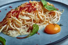 Classic pasta carbonara with yolk on a plate. Pasta laid out on a blue plate on a dark background. Concept of Italian. Cuisine, beautiful serving dishes, close royalty free stock photo