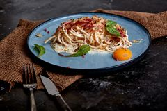 Classic pasta carbonara with yolk on a plate. Pasta laid out on a blue plate on a dark background. Concept of Italian. Cuisine, beautiful serving dishes, close royalty free stock photography