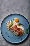 Classic pasta carbonara with yolk on a plate. Pasta laid out on a blue plate on a dark background. Concept of Italian. Cuisine, beautiful serving dishes, close stock photo