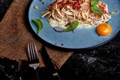 Classic pasta carbonara with yolk on a plate. Pasta laid out on a blue plate on a dark background. Concept of Italian. Cuisine, beautiful serving dishes, close royalty free stock images