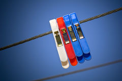 Classic Pegs on Line. Generic pegs on a washing line in clear blue sky stock photos