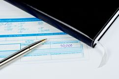 Classic pen on deposit slip. Classic pen with notebook on deposit slip over white Royalty Free Stock Image