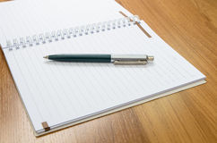 Classic pen and notebook on wooden desk Stock Photos
