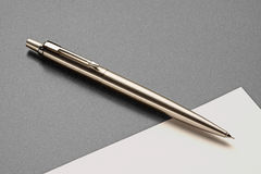 Classic pen and paper. Classic silver pen and blank paper on grey surface royalty free stock photography