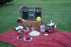 A classic picnic basket with fruits, meringue, vegetables, red wine, rose wine and champagne royalty free stock image