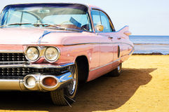 Classic pink Cadillac at beach royalty free stock photos