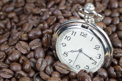 Classic pocket watch on coffee beans background Royalty Free Stock Image