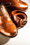 Classic polished men's brogues and brown belt Stock Images