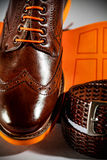 Classic polished men's brogues with orange sole and brown belt.  Royalty Free Stock Images