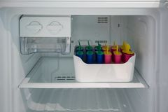Classic popsicle mold set in freezer container for homemade ice. Lolly in summer stock photography
