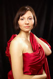 Classic portrait. Portrait of a young women in a red dress on a dark background Royalty Free Stock Photos