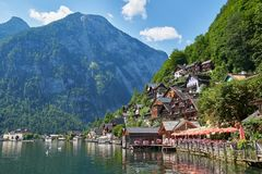 Classic postcard view of famous Hallstatt lakeside town reflecting in Hallstattersee lake in the Austrian Alps in scenic beautiful stock image