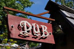 Classic pub sign. A classic pub sign mad of wood and metal hangs above the entrance Stock Photography
