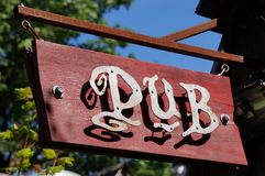 Classic pub sign. A classic pub sign mad of wood and metal hangs above the entrance Stock Photos