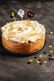 Classic Pumpkin Cheesecake with Marshmallow Meringue Topping decorated with Halloween toppers. Dessert for Halloween and Thanksgiv royalty free stock photos