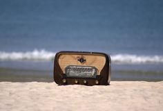Classic radio on a beach. A classic radio on a white sand beach with the sea and waves in the background Royalty Free Stock Photo