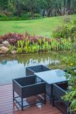Classic rattan chairs and table on wooden balcony beside the small beautiful lake in a green plant garden royalty free stock photos