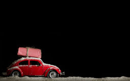 Classic red car deliverling Santa Clause presents in snowy weather stock photo