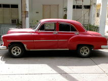 Classic Red Car. In front of a Cuban building Royalty Free Stock Photography