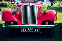 Classic Red Car on Green Grass Stock Images