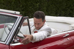 Classic red convertible and driver. A well dressed man in a classic red convertible Royalty Free Stock Image