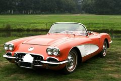 Classic red corvette car. Open top classic corvette car standing outside in a meadow royalty free stock photography
