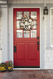 Classic red door to a white home Stock Images