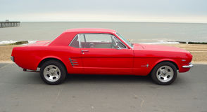Classic Red Ford Mustang parked on seafront promenade. Stock Photos