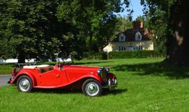 Classic Red MG Motor Car Parked on Village Green. Stock Photos