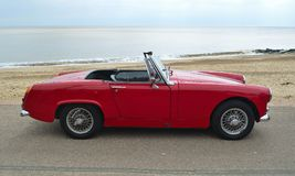 Classic  Red  MG Roadster  Car  parked on seafront promenade with sea in background. Stock Photography