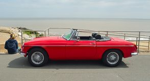 Classic  Red  MG Roadster  Car  parked on seafront promenade with sea in background. Royalty Free Stock Images