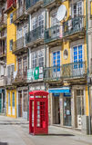 Classic red phone booth and colorful houses in Porto Stock Image