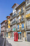 Classic red phone booth and colorful houses in Porto Royalty Free Stock Photography
