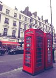 Classic red phone box in London. Public red phone box in London, England Royalty Free Stock Photo