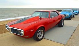 Classic Red Pontiac Firebird motor car  parked on seafront promenade. FELIXSTOWE, SUFFOLK, ENGLAND - AUGUST 27, 2016:  Classic Red Pontiac Firebird motor car Royalty Free Stock Photos