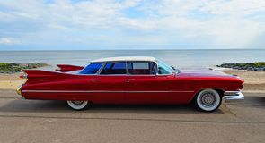 Classic Red 1950`s 4 door Cadillac  motor car parked on seafront promenade. FELIXSTOWE, SUFFOLK, ENGLAND - MAY 05, 2019: Classic Red 1950`s 4 door Cadillac stock image
