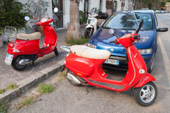 Classic red Vespa scooters parked on a roadside Royalty Free Stock Photography