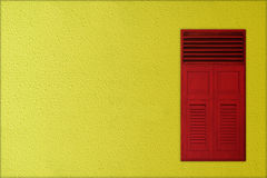 Classic red wooden windows on yellow rough cement background Royalty Free Stock Image