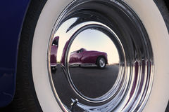 Classic Reflection. A classic car reflects in the chrome hubcap of another classic car royalty free stock photography