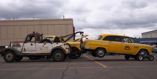 Classic Restored Taxi And Towtruck. Classic restored taxi being pulled by an antique tow truck Royalty Free Stock Photos