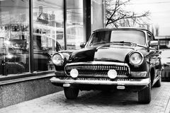 Classic retro car. In street near shop show-window, black and white Royalty Free Stock Images