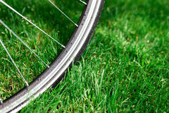 Classic road bicycle wheel close-up photo in the summer green grass meadow field. Travel background Royalty Free Stock Images