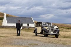 1935 classic Rolls Royce 20/25. A 1935 classic Rolls Royce 20/25 waits near the Holy Cross Church Eglwys Y Grog, while it`s chauffeur stands near by. Mwnt royalty free stock photos