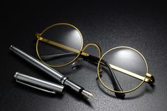Classic round eyeglasses. Gold frame classic round eyeglasses and fountain pen on the black background royalty free stock images