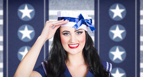 Classic 40s pin up navy girl saluting with smile. Face of a classic 40s pin up navy girl saluting with adorable smile on military blue colours background Stock Photo