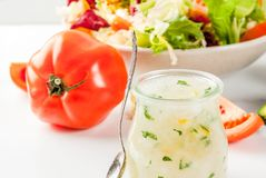Classic salad dressing, homemade ranch dressing with olive oil h. Erbs and lemon, with fresh vegetables on white marble table, copy space royalty free stock photos