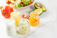 Classic salad dressings. Set of classic salad dressings - honey mustard, ranch, vinaigrette, lemon & olive oil,  on white marble table, copy space Royalty Free Stock Photos